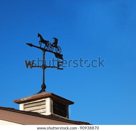 A rustic  iron weather vane featuring a horse and buggy perched atop an old building against a blue sky.