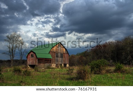 A rustic old barn under stormy skies.