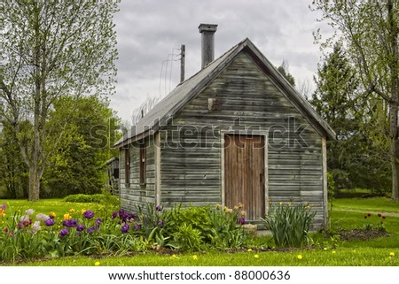 A rustic quaint country garden shed with a row of flowers around it. - stock photo