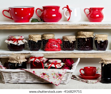 A rustic style. Ceramic tableware and kitchenware in red on the shelves. - stock photo