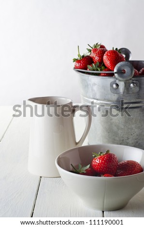 A rustic table scene of freshly harvested strawberries, just harvested.  Includes a tin pail of strawberries, a cream jug and a bowl of served strawberries. - stock photo