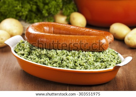 A rustic table with a dish with 'Boerenkool met worst' or kale with smoked sausage, a traditional Dutch meal. - stock photo