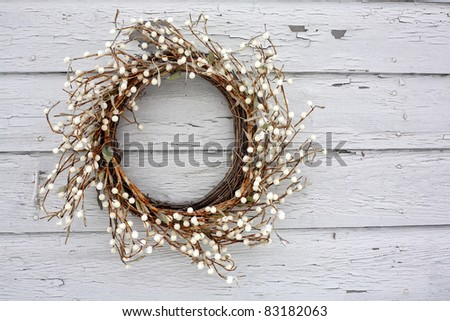 A rustic vine and berry wreath hanging on  a white painted clap board house.  This exterior wreath is snow and ice covered. - stock photo