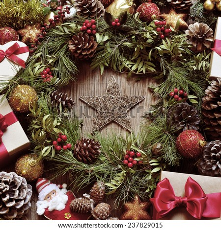 a rustic wooden table full of gifts, and christmas ornaments, such as a natural wreath with branches, berries and pine cones, or christmas balls and stars , with a retro effect - stock photo
