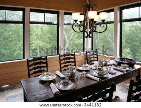 A rustic yet classy outdoor dining setup on a screened porch.