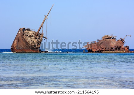 A rusting metal shipwreck aground on a tropical coral reef - stock photo