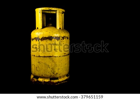 A rusting propane gas tank isolated against a black background - stock photo