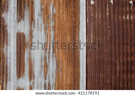 A rusty and weathered looking piece of corrugated metal. - stock photo