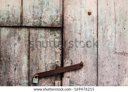 a rusty and weathered old door closed with a padlock - stock photo