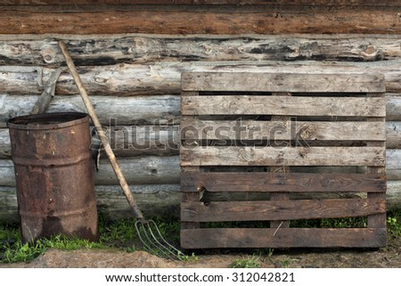 A rusty barrel, a hayfork and a pallet on the wood wall background. - stock photo