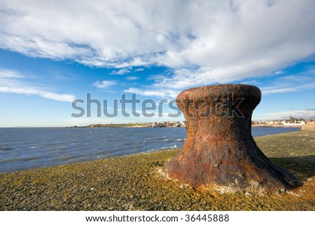 A rusty bollard on a sea wall in early morning light with blue skies. Photo taken in Anstruther, Scotland.