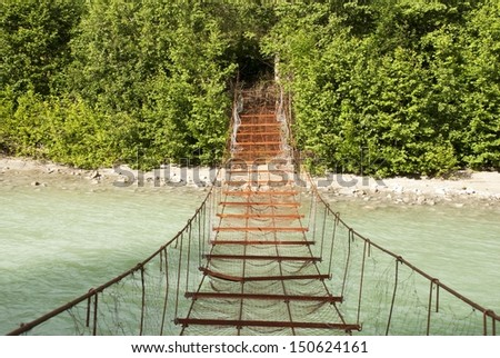 A Rusty Dangerous Bridge Leads over a Turquois River into the Woods - stock photo