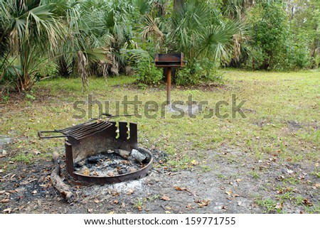 A rusty fire pit with ashes, and a rusty BBQ stand, in a remote tropical camp site. - stock photo