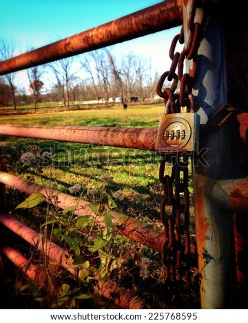 A rusty gate with a combination lock attached to a rusty chain. - stock photo
