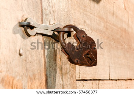 A rusty old lock on a wood door