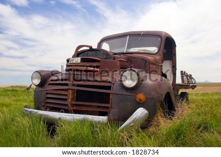 A rusty old pickup truck sits derelict in a field - stock photo