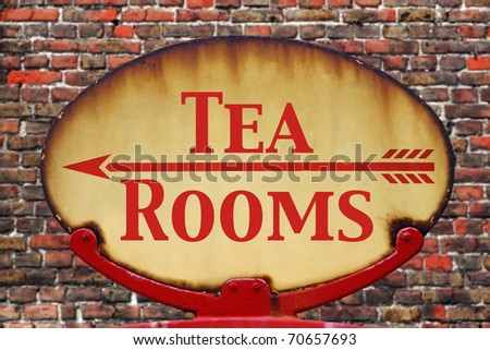A rusty old retro arrow sign with the text Tea rooms