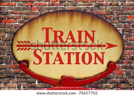 A rusty old retro arrow sign with the text Train station - stock photo