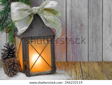 A rusty, weathered lantern with clouded glass and a candle glowing inside is decorated with a seasonal bow. There is evergreen, pinecones and snow on the wooden table with wood background. Copy space. - stock photo