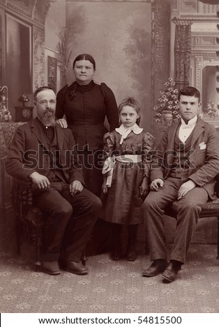 A 1800's antique vintage portrait photograph of a family posing for the camera. It is a studio formal photo of a Quaker family.