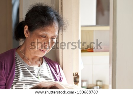 A 50s asian woman reading newspaper at home - stock photo