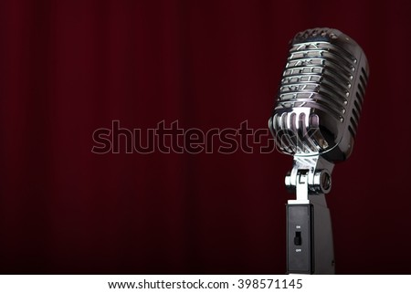 A 1950's microphone on a stage in front of a red curtain