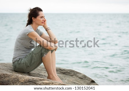 A sad and depressed woman sitting by the ocean deep in thought. - stock photo