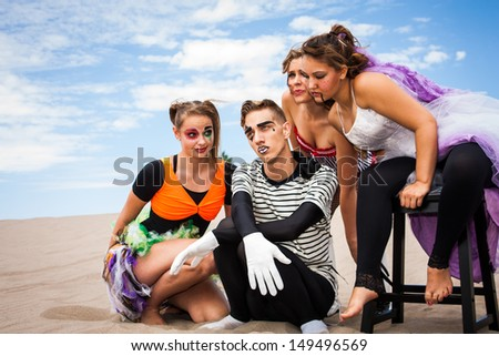 A sad and pensive young man surrounded by attentive young ladies