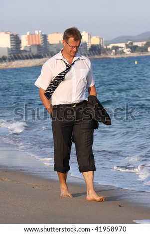 A sad businessman is walking on the beach - stock photo