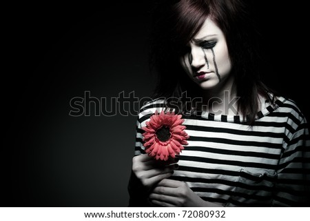 a sad female mime clown with a red flower