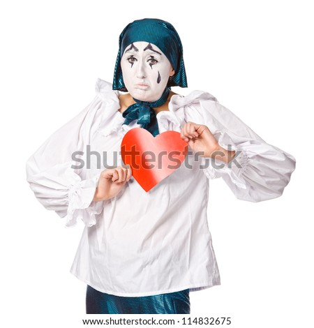 a sad female mime clown with a red heart. Isolated over white - stock photo