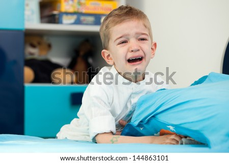 A sad five year old child sitting next to his bed with holding a pillow and crying - stock photo