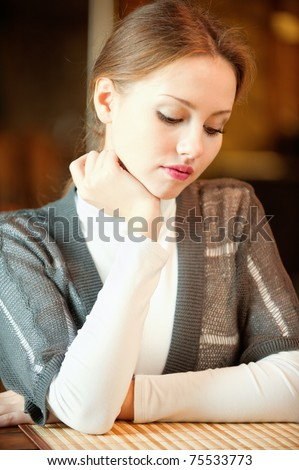 A sad girl sitting at a table in a cafe and looks down. - stock photo