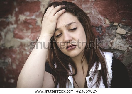 A Sad girl with motional face brick background - stock photo