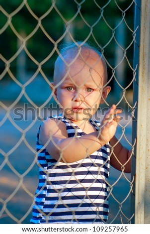 a sad little boy looks over the fence - stock photo