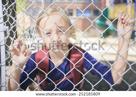 A sad little girl at school playground - stock photo