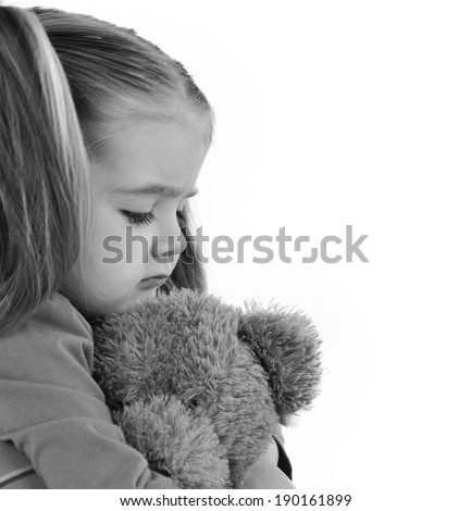 A sad little girl is holding a stuffed teddy bear on a white isolated background for a timeout or emotion concept. - stock photo