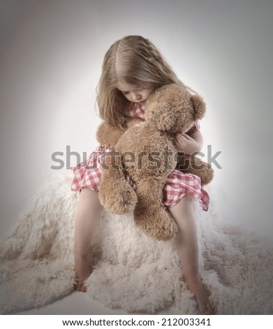 A sad little girl is holding a stuffed teddy bear on an isolated background for a timeout or emotion concept.  - stock photo