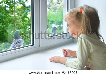A sad little girl looks at a pigeon outside the window - stock photo