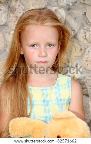 A sad little girl 5 years old, with a teddy bear - stock photo