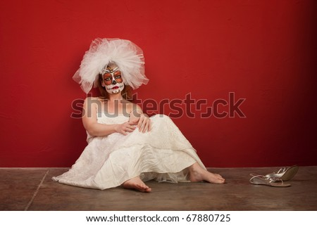 A sad looking bride in makeup for All Souls Day with shoes off sits on the ground - stock photo
