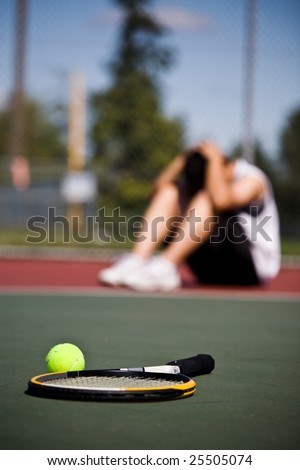 A sad male tennis player sitting down in disappointment after defeat - stock photo