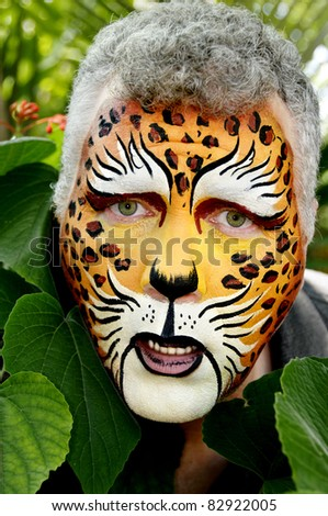 A sad man with his face painted to look like a leopard.