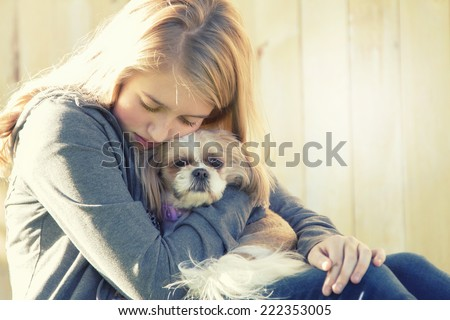 A sad or depressed teenage girl hugging a small dog in an outdoor setting - stock photo