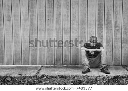 A sad or thinking teen boy sitting against a wall. - stock photo