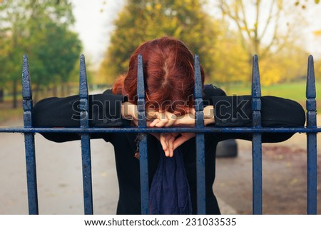 A sad woman is resting her head on a gate in the park in autumn - stock photo