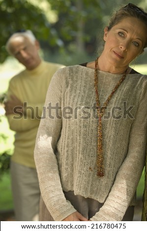 A sad woman, man blurred in the background. - stock photo