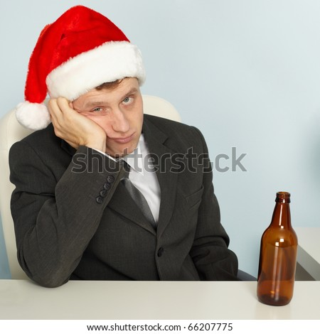A sad young man suffering from a hangover after Christmas - stock photo