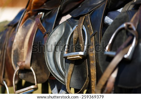 A saddles laying on the rustic fence in warm sunlight - stock photo