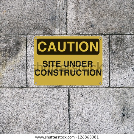 A safety sign mounted on a brick wall. Applicable to workplace safety or website downtime status.
